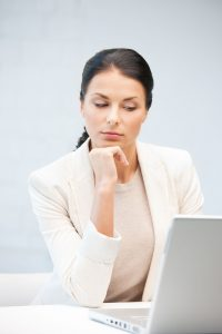 picture of pensive woman with laptop computer.